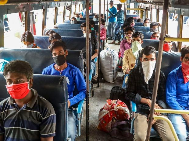 Migrant workers travel in bus to a railway station before boarding a train in Kozhikode
