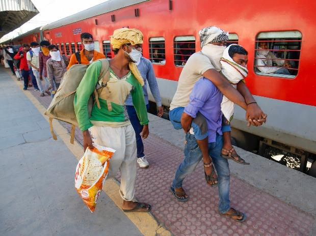 Migrant workers walk to board a special train to return to Agra, during a nationwide lockdown, at a railway station in Ahmedabad