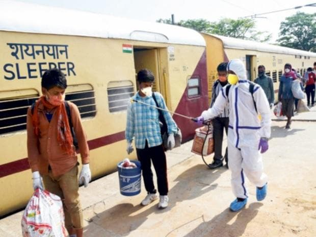 A health worker sanitises migrants, who arrived from Jaipur in a Shramik Special train, at Danapur junction near Patna. JD(U) leader and Bihar CM Nitish Kumar was earlier opposed to the idea of bringing labourers back to their home states  Photo: PTI