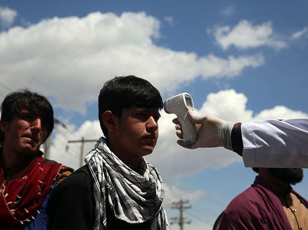 A health worker checks the temperature of car passengers in an effort to help prevent the spread of the coronavirus, as they enter the city in the Paghman district of Kabul, Afghanistan.