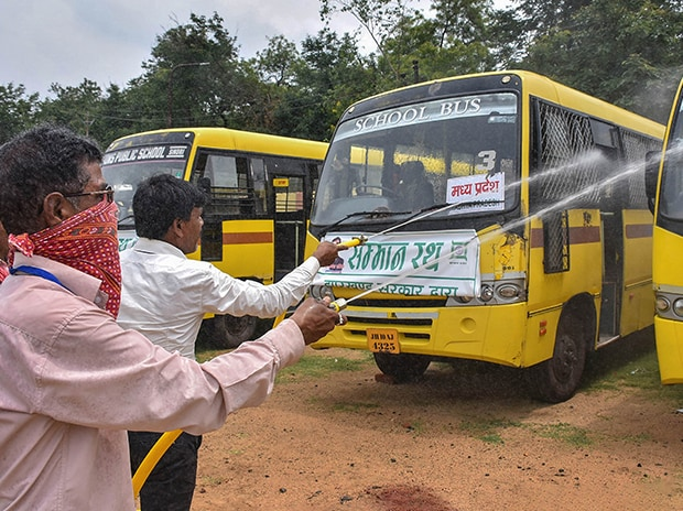 Workers sanitise buses meant to transport migrant workers from different states to their native places, during the ongoing nationwide lockdown, at Golf ground in Dhanbad. Photo: PTI