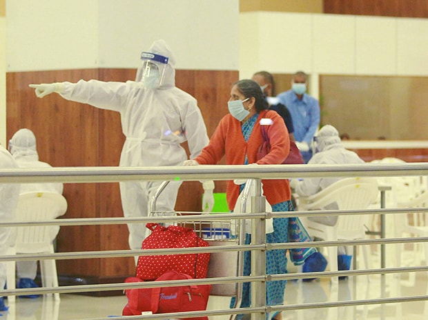 Medics screen passengers after an Air India Express flight brought stranded Indian nationals from Abu Dhabi, UAE, as part of the repatriation exercise 'Vande Bharat Mission', at the airport in Kochi. Photo: PTI