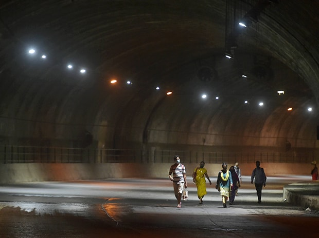 Migrants from Raigad district of Maharashtra walk through a tunnel along the easter freeway, in Mumbai. Photo: PTI
