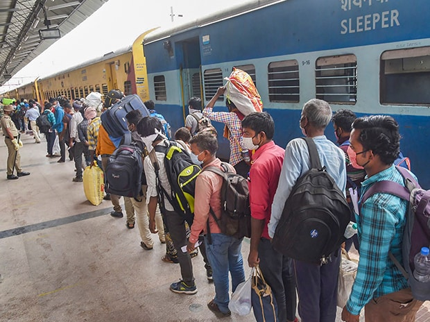 Migrants flout social distancing norms as they gather outside a registration camp to travel back to their native places, during the ongoing COVID-19 nationwide lockdown, in Jalandhar. Photo: PTI