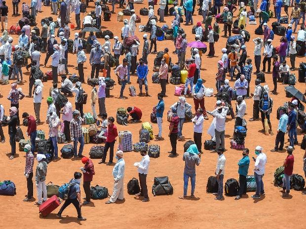 Migrants waiting in queues to board buses departing for railway terminus, from where they will board trains to travel to their native places, during the ongoing nationwide Covid-19 lockdown, at Wadala in Mumbai. Photo: PTI
