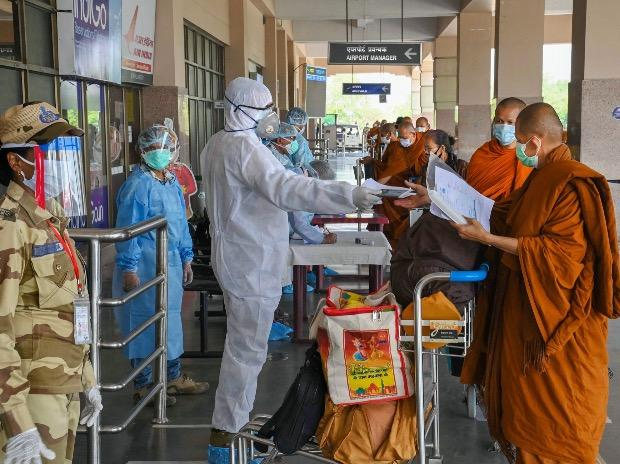 A security man wearing a protective suit checks documents of stranded Buddhist monks from Thailand at Gaya airport, during the ongoing Covid-19 lockdown, in Gaya. Photo: PTI
