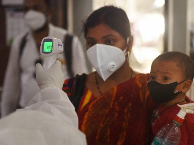 Health workers conduct thermal screening of passengers who have arrived from Delhi by a special train at Howrah station, during the ongoing COVID-19 nationwide lockdown, in Kolkata