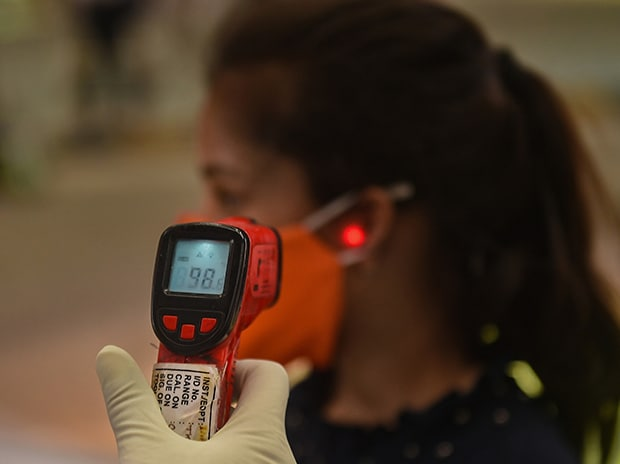 A medic conducts thermal screening of a passenger waiting to board a train to Delhi at Howrah station, during the ongoing Covid-19 nationwide lockdown, in Kolkata. Photo: PTI