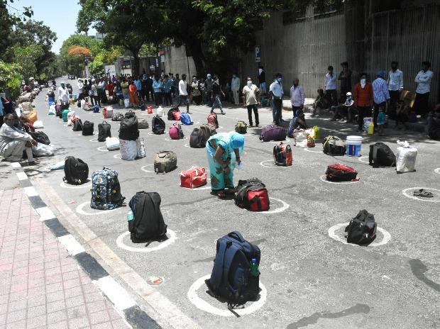 Migrants keep their luggage to reserve their spot in a queue, while they sit under shade, before boarding a bus to the railway station, during the ongoing nationwide COVID-19 lockdown, in Surat