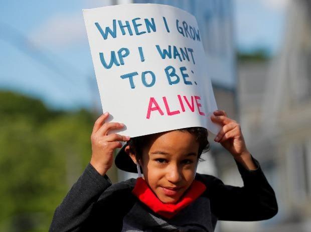 Adam Neves, six ans, tient une pancarte lors d'un rassemblement suite au décès de George Floyd, en garde à vue à Minneapolis, à Boston, Massachusetts, États-Unis.
