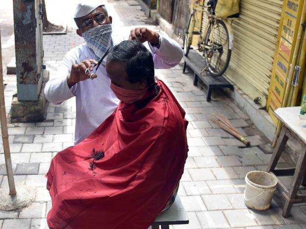 Barber shops and salons reopen in Mumbai: Nathu Bhawar attends to a customer at Fort in Mumbai