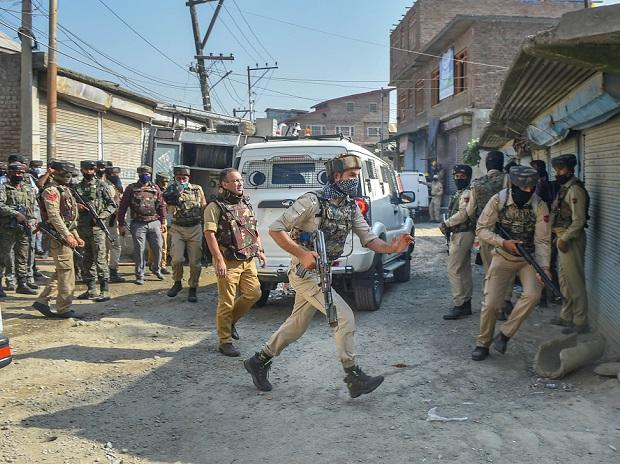 Security personnel take position during an encounter with militants, at Batamaloo in Srinagar. Photo: PTI