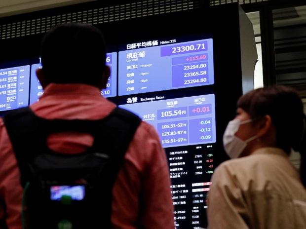 TV crews talk in front of a large screen showing stock prices at the Tokyo Stock Exchange in Tokyo. Photo: Reuters