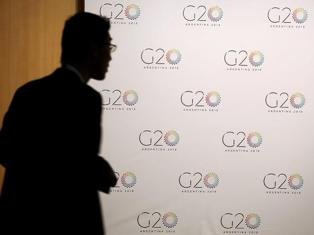 A man stands next to a board with the G20 Meeting of Finance Ministers logo in Buenos Aires, Argentina. Photo: Reuters