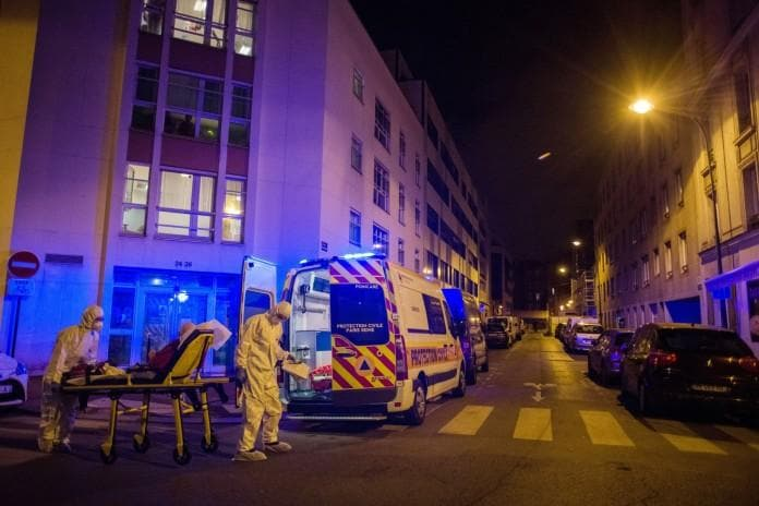 Health workers wheel a Covid-19 patient into an ambulance in Paris