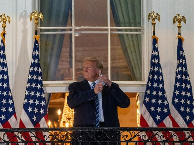 After returning from Walter Reed, President Donald Trump ascended to the Blue Room balcony where he removed his mask and acknowledged supporters and White House staff. Photo: Bloomberg