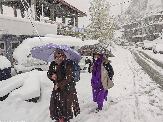 Locals walk along a snow-laden street in Lahaul-Spiti district's Keylong during snowfall