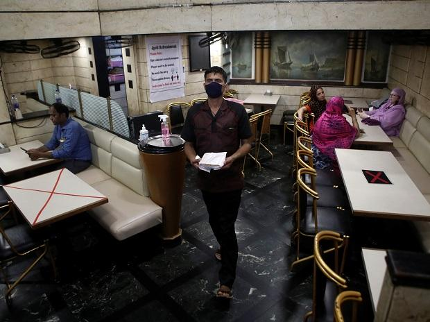 A waiter walks past tables that have been blocked to maintain social distancing at restaurant after they reopened amidst the spread of the coronavirus disease (COVID-19) in Mumbai. Photo: Reuters