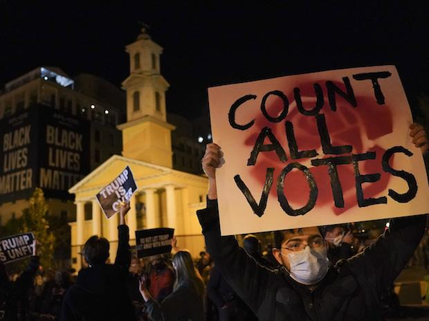 A demonstrator holds up a sign while waiting for election results at Black Lives Matter Plaza, Tuesday, Nov. 3, 2020, in Washington. (AP Photo/John Minchillo)