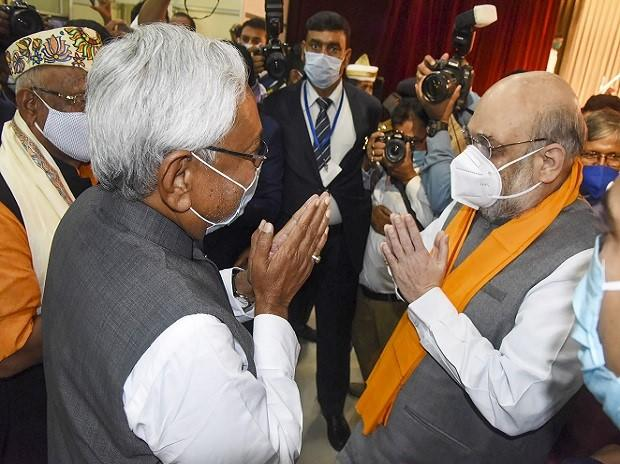 Union Home Minister Amit Shah greets Bihar Chief Minister Nitish Kumar after the oath-taking ceremony at Raj Bhawan in Patna, Monday, Nov. 16, 2020. (PTI Photo)