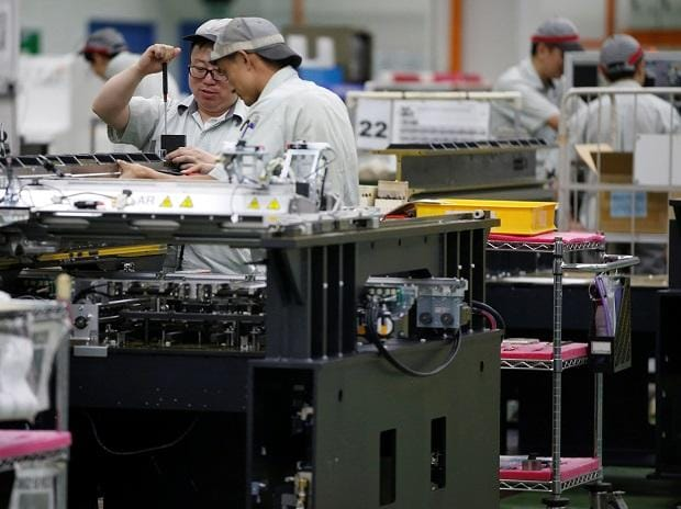 Employees are seen by their workstations at a printed circuit board assembly factory in Singapore. Photo: Reuters