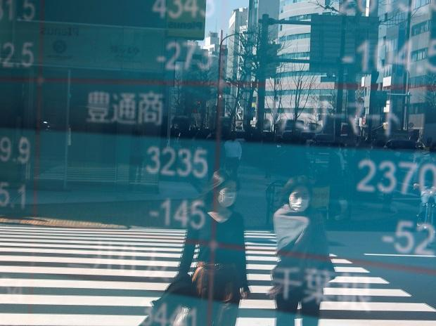 People wearing protective face masks, following an outbreak of the coronavirus, are reflected on a screen showing Nikkei index, outside a brokerage in Tokyo. Photo: Reuters