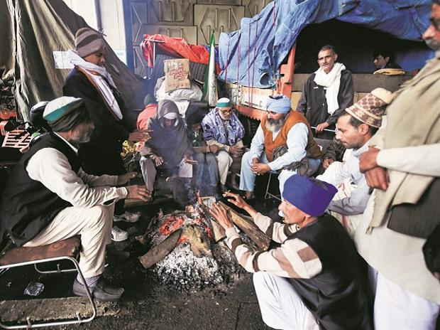 Farmers sit around a bonfire to keep themselves warm during their protest against the farm laws, at Ghazipur Border on Sunday. File Photo: PTI
