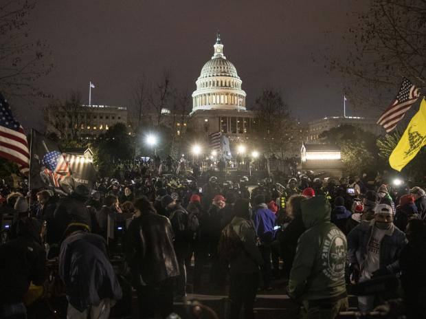 Law enforcement officers guard the U.S. Capitol building after demonstrators earlier stormed the building on Jan. 6. Photographer: Victor J. Blue/Bloomberg