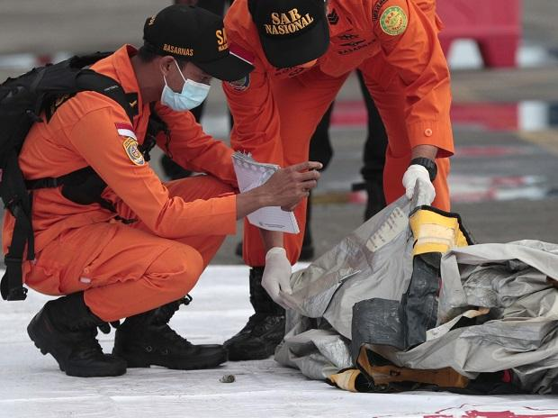 Rescuers inspect debris found in the waters around the location where a Sriwijaya Air passenger jet has lost contact with air traffic controllers shortly after the takeoff