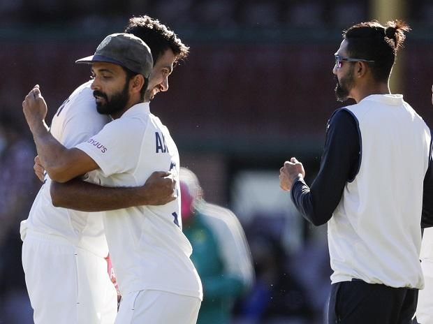 R Ashwin is embraced by Ajinkya Rahane, as teammate Mohammed Siraj, right, watches following play on the final day of the third cricket test between India and Australia at the Sydney Cricket Ground