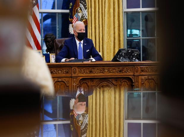 President Biden signs executive orders inside the Oval Office at the White House in Washington