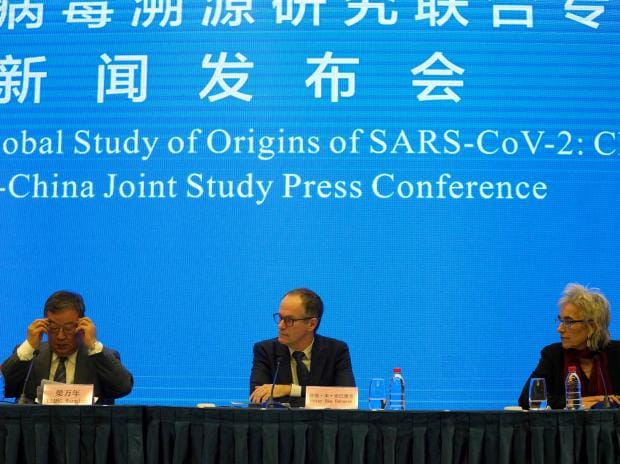 Marion Koopmans, right, and Peter Ben Embarek, center, of a World Health Organization team look over at their Chinese counterpart Liang Wannian, left, during a WHO-China Joint Study Press Conference, Tuesday, Feb. 9, 2021. (AP Photo/Ng Han Guan)