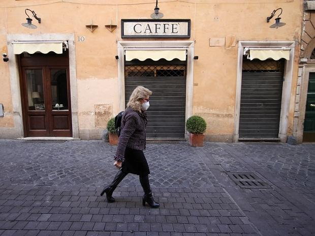A woman walks past a closed cafe as Rome becomes a red zone, going into lockdown, as the country struggles to reduce the coronavirus disease (COVID-19) infections, in Rome