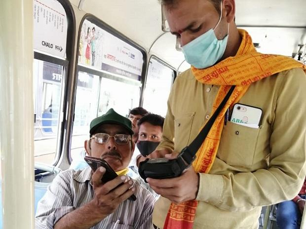 A passenger and bus conductor using Chalo's 'Sound QR', an ultrasonic sound technology for verification of mobile tickets