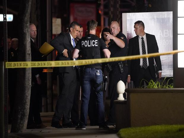 Investigators gather outside an office building where a shooting occurred in Orange, California