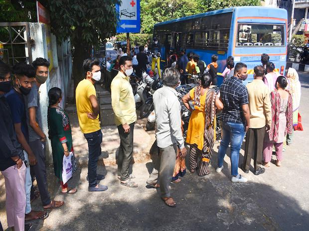 People wait in queue to collect medicines from Arogya Rath, a government initiative, in Surat | Photo: PTI