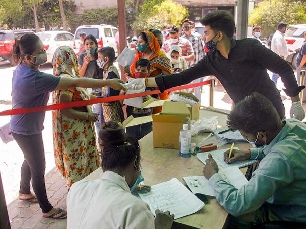 People wait to collect Covid-19 testing kits outside a District Hospital, in Noida | Photo: PTI