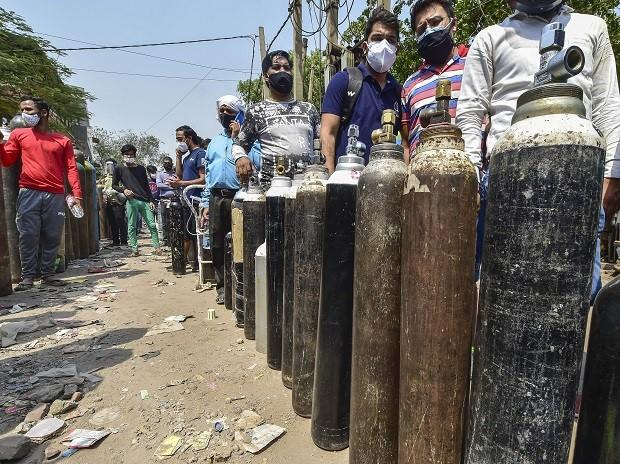 Family members of Covid-19 patients wait outside an oxygen-filling centre to refill their empty cylinders in New Delhi.