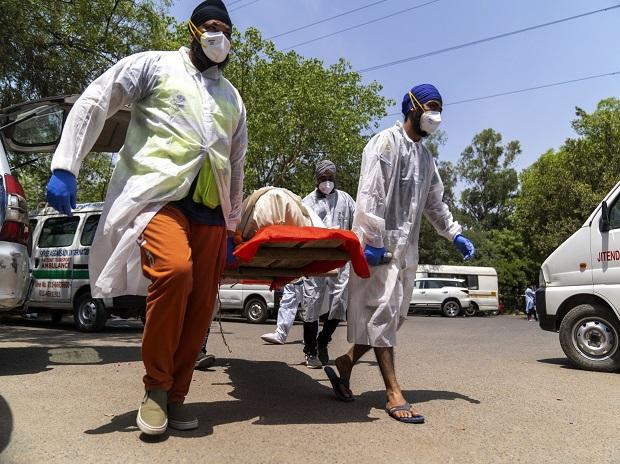 People carry the body of a deceased Covid-19 patient into a crematorium
