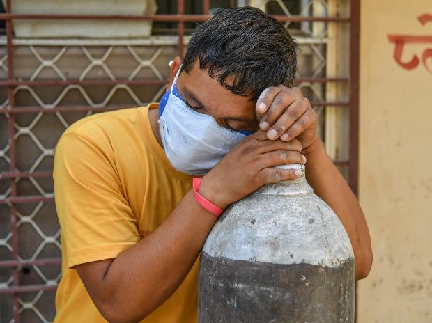 A relative of a Covid-19 patient rests in Ajmer as he waits to refill a cylinder with medical oxygen