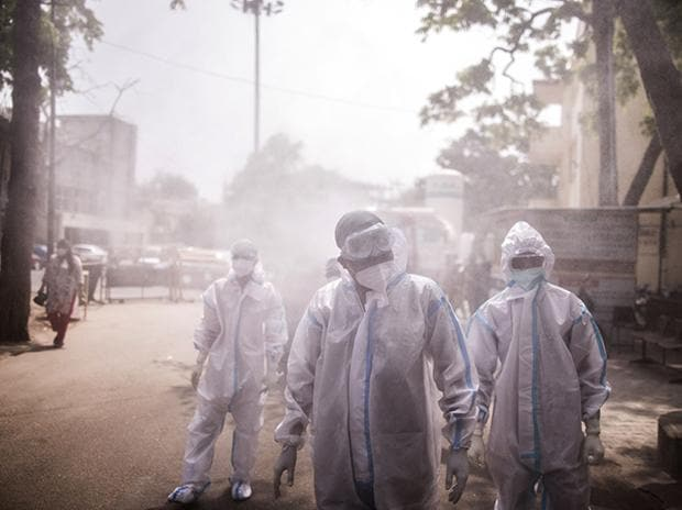 Frontline workers are sprayed with disinfectant at a Covid-19 Care Center set up at the Sarojini Naidu Medical College (SNMC) in Agra, Uttar Pradesh, India. Photo: Bloomberg