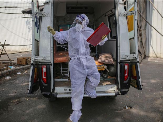 A health worker exits an ambulance outside a quarantine center. (Photo: Bloomberg)