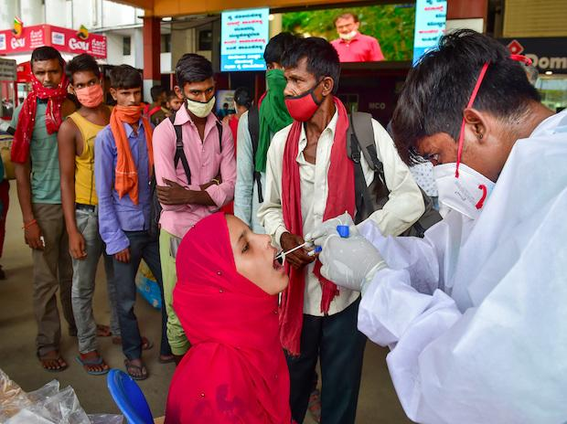 A health worker at a railway station in Bengaluru tests a passenger for Covid-19 on Monday, Aug. 9, 2021. (PTI Photo/ Shailendra Bhojak)