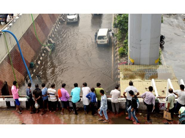 People look on from above as vehicles wade through a waterlogged road after rain at Azadpur area in New Delhi (Photo: PTI)