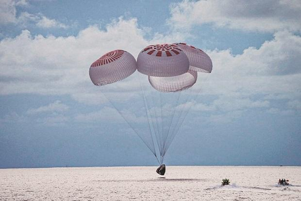 Capsule carrying the crew parachutes into the Atlantic Ocean