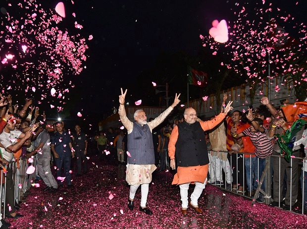Bhartiya Janata Party workers welcome Prime Minister Narendra Modi as he, along with BJP President Amit Shah, arrives at the party headquarters to celebrate the party's victory in the 2019 Lok Sabha elections