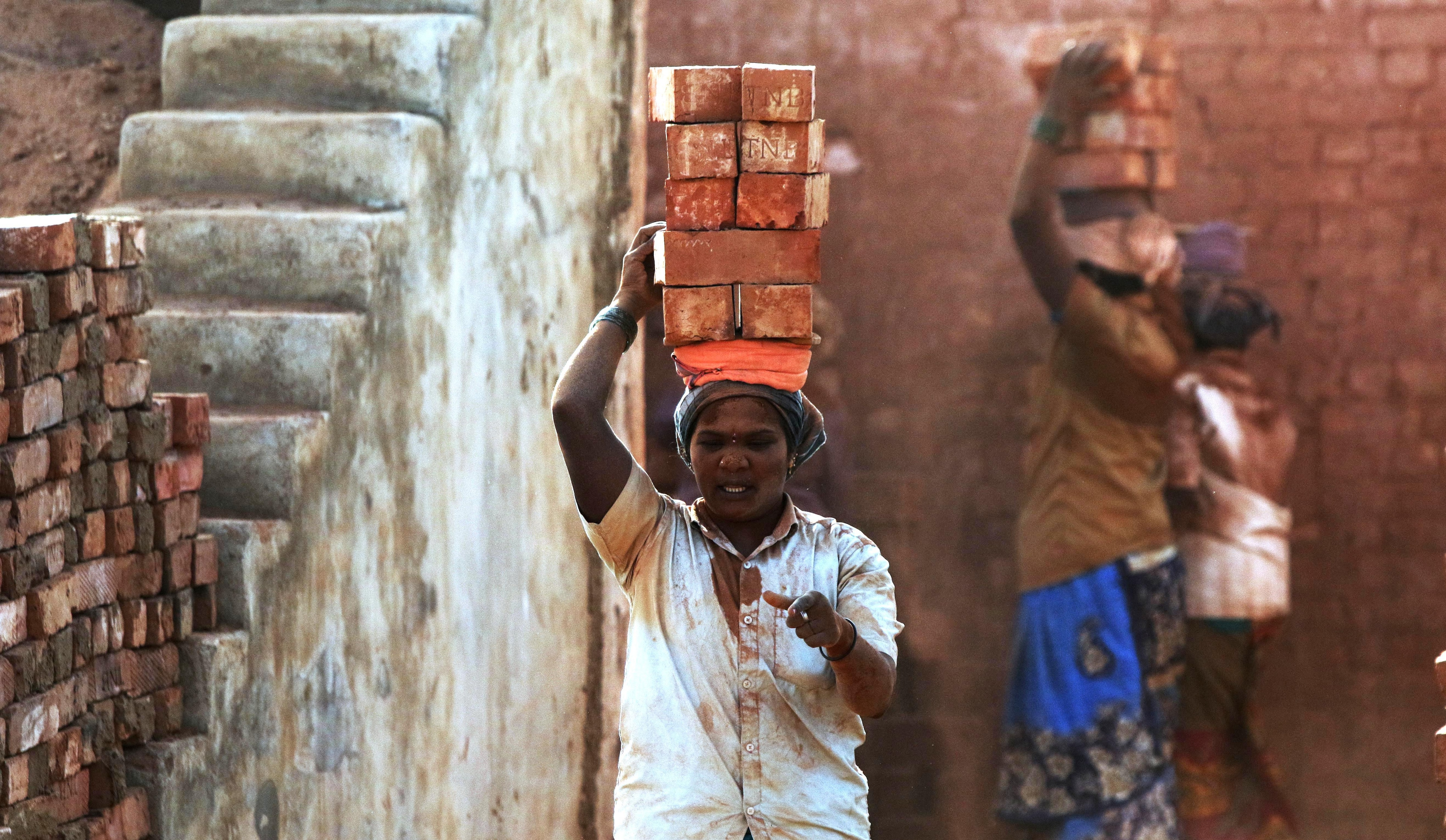 A woman labourer carries bricks at a brick kiln after relaxation in the 5th lockdown, in Chennai on Thursday.