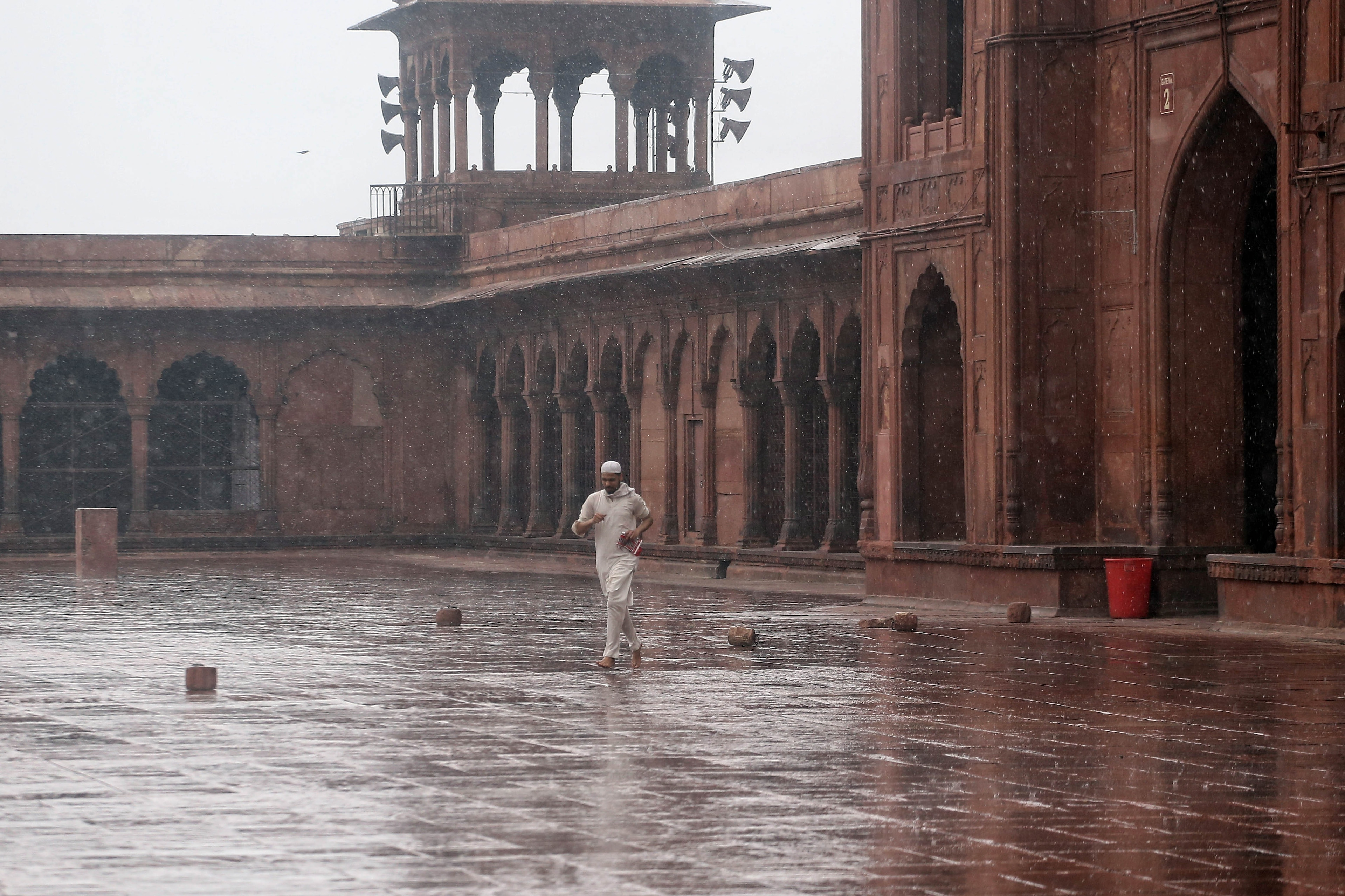 A man walks during the rain at Jama Masjid in New Delhi. Photo: ANI