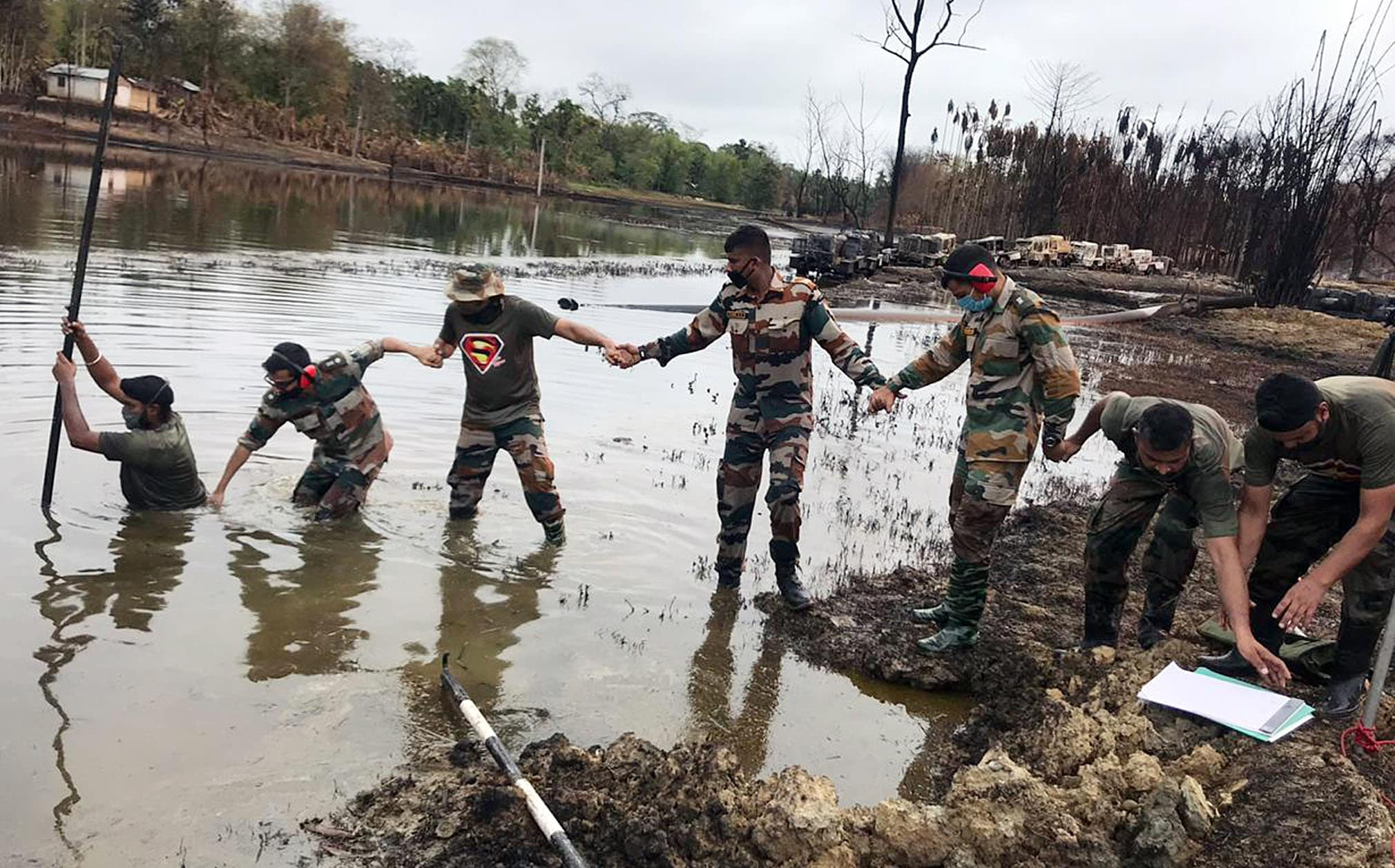 Indian army personnel assessing at ground zero Baghjan near the blowout well, as they helping to build a temporary pontoon bridge of around 150 meter length over a water body adjacent to the well, in Tinsukia on Monday.