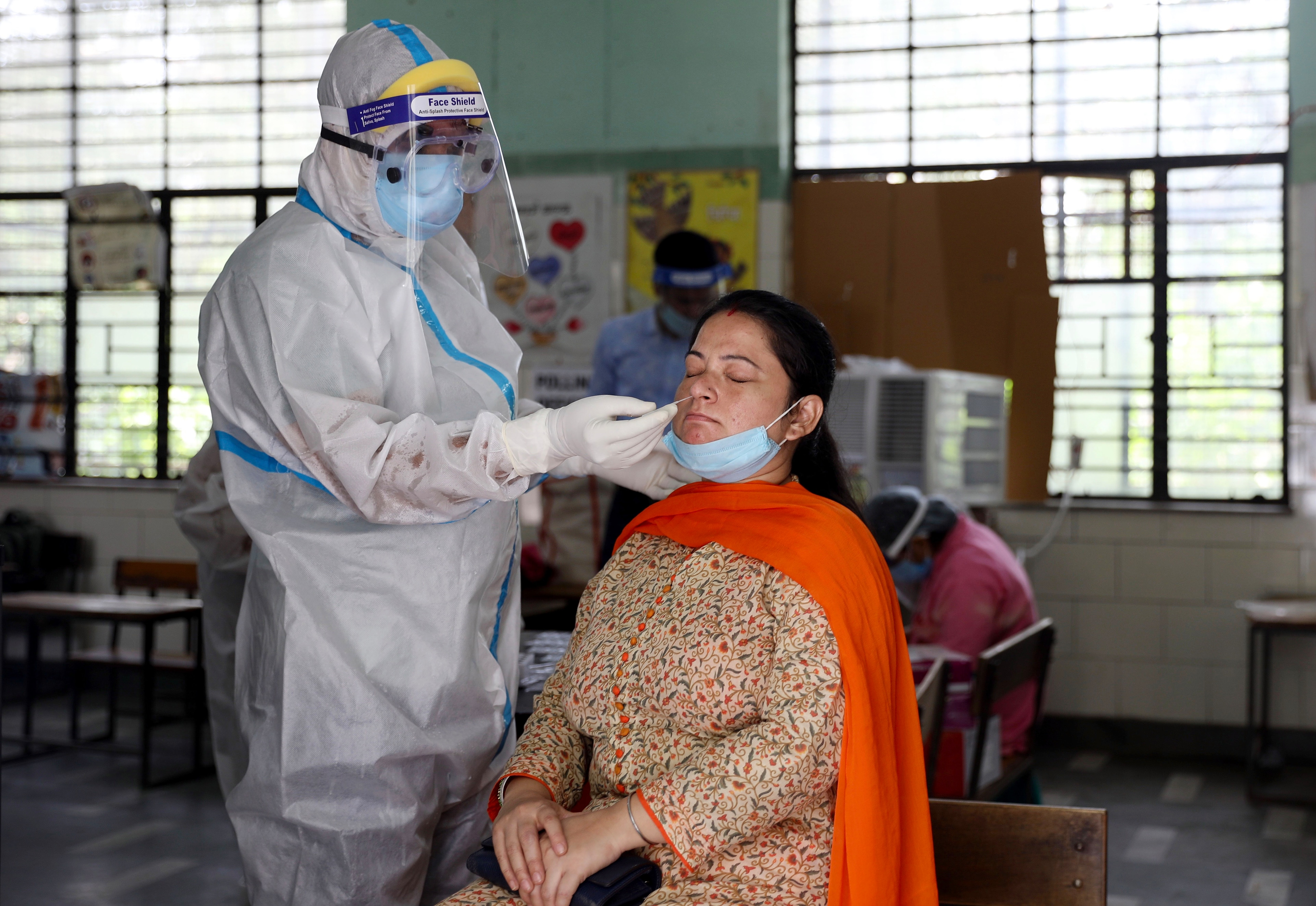A health official collects a swab sample from a woman to test for the Covid-19 inside a government school, in New Delhi. Photo: ANI